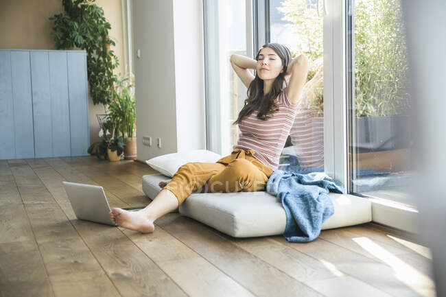 Relaxed young woman sitting at the window at home with laptop — Stock Photo