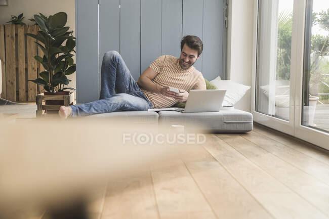 Junger Mann sitzt auf Matratze, benutzt Laptop und macht sich Notizen — Stockfoto