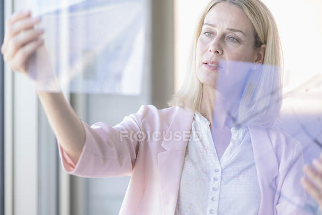 Businesswoman holding transparent foil — Stock Photo