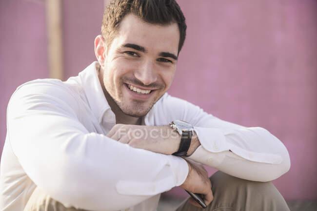 Portrait de jeune homme souriant devant un mur rose — Photo de stock
