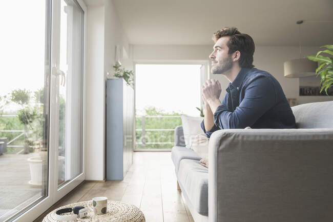 Young man sitting on couch at home, looking out of window — Stock Photo