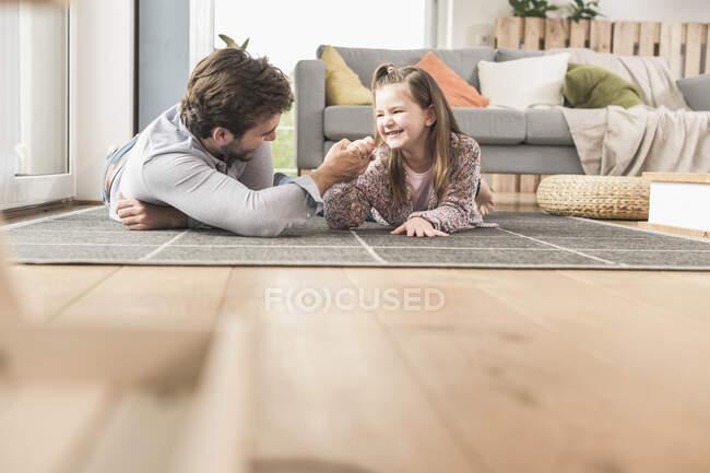 Молодой человек и маленькая девочка лежат на земле, армрестлинг — стоковое фото