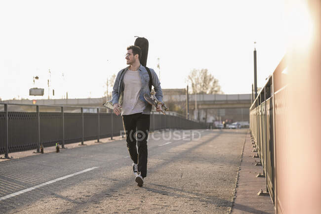 Smiling young man with guitar case and skateboard walking on a bridge in the city — Stock Photo