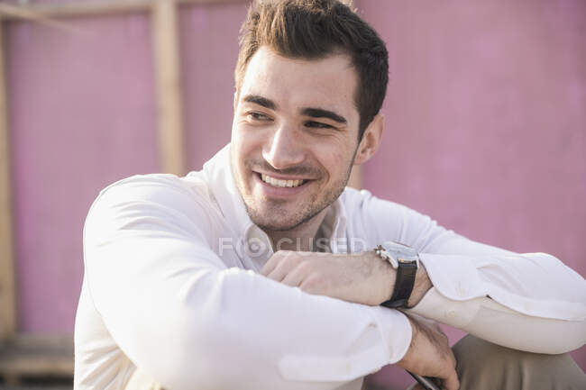Портрет улыбающегося молодого человека перед розовой стеной — стоковое фото