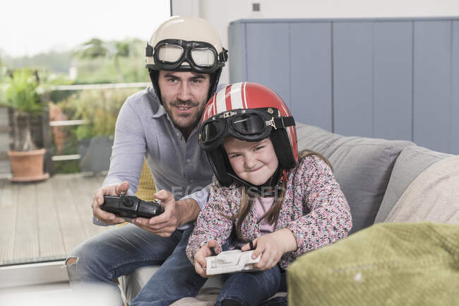 Young man and little girl wearing biker helmets, playing racing game with gaming consoles — Stock Photo