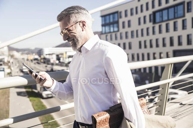 Улыбающийся взрослый бизнесмен, использующий мобильный телефон в городе — стоковое фото