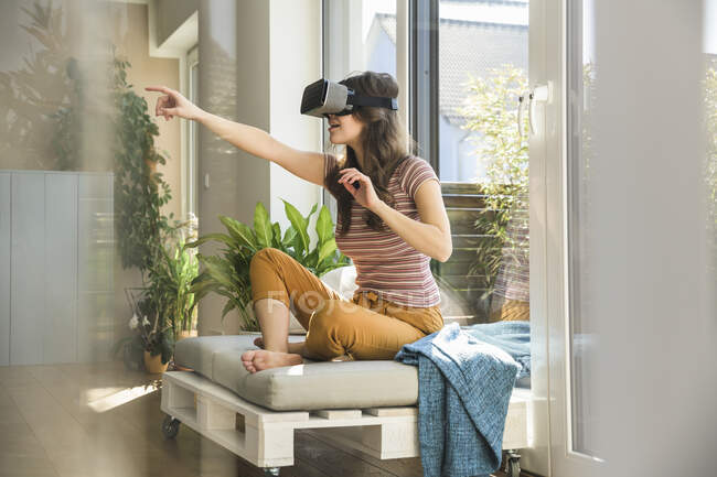 Young woman sitting at the window at home wearing VR glasses — Stock Photo