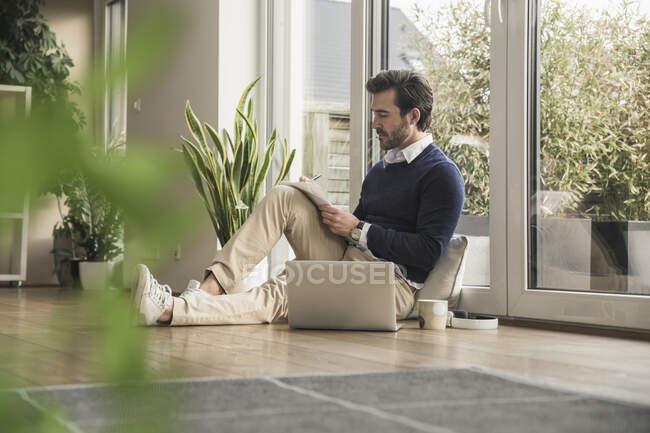Jeune homme assis dans le salon, appuyé sur la fenêtre, travaillant avec un ordinateur portable, prenant des notes — Photo de stock