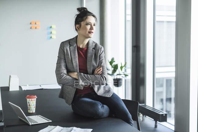 Безробітна жінка сидить за столом у офісі і дивиться убік. — стокове фото