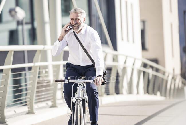 Щасливий дорослий бізнесмен розмовляє по мобільному телефону і їздить на велосипеді по мосту в місті. — стокове фото
