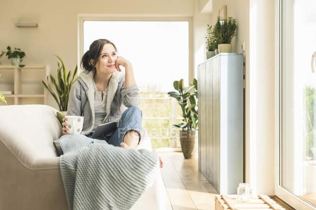 Lächelnde Frau mit Becher und Tablet auf dem heimischen Sofa — Stockfoto