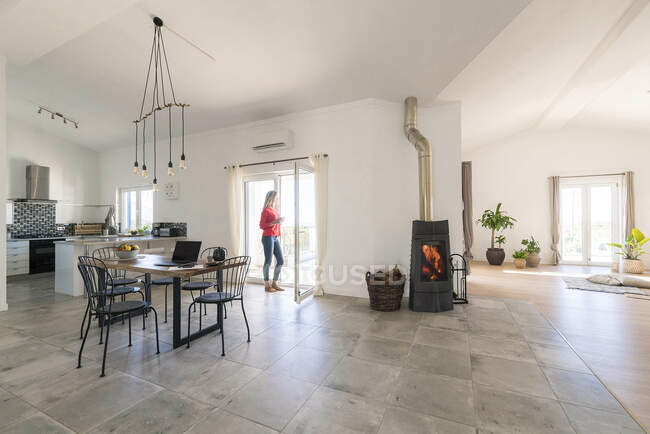 Woman standing in door frame of modern living room with fireplace — Stock Photo