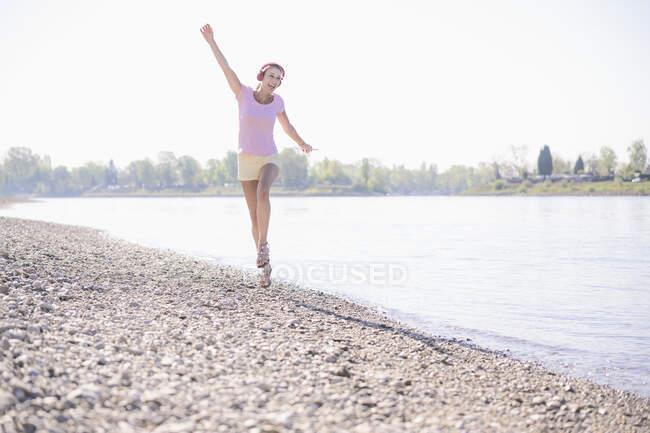 Щаслива зріла жінка слухає музику з навушниками на березі річки. — стокове фото