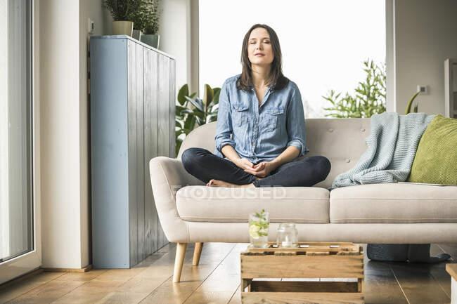 Femme assise sur le canapé à la maison les yeux fermés — Photo de stock
