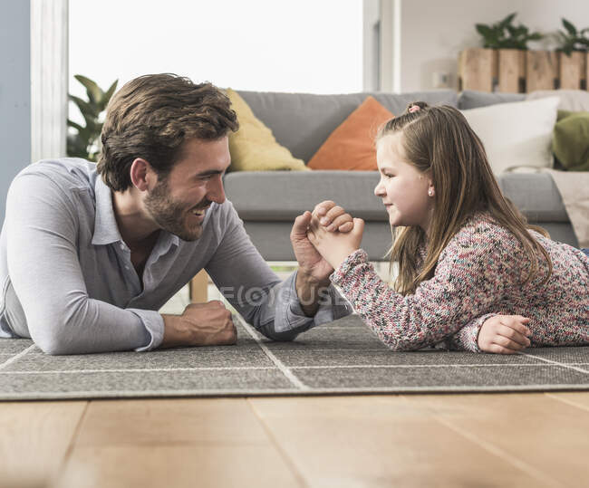 Young man and little girl lying on ground, arm wrestling — Stock Photo