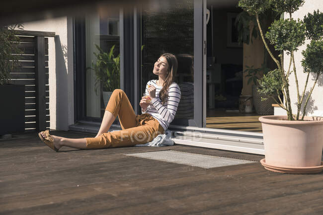 Jeune femme assise sur la terrasse à la maison profitant du soleil — Photo de stock