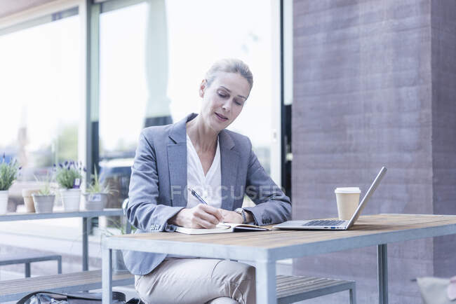 Businesswoman working at an outdoor cafe — Stock Photo