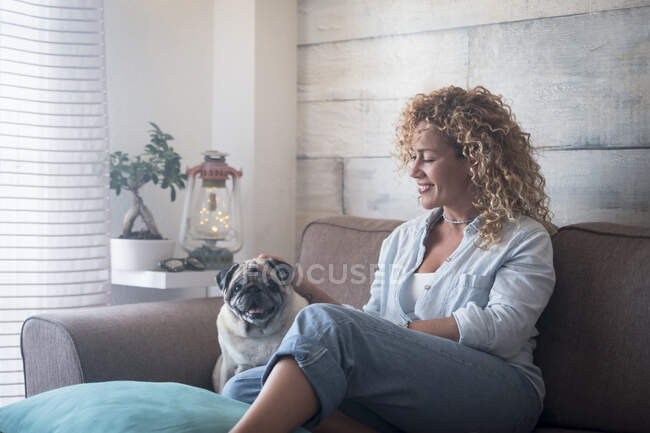 Woman sitting on couch at home petting pug dog — Stock Photo