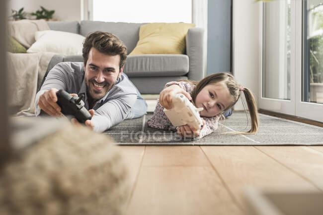 Молодой человек и маленькая девочка играют в компьютерные игры с игровой консолью — стоковое фото