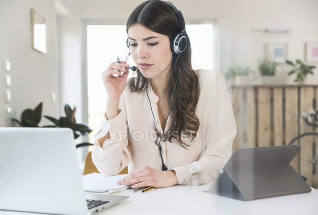 Young woman sitting at table at home wearing a headset — Stock Photo