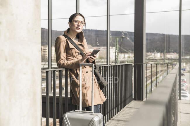 Portrait de femme d'affaires avec bagage et téléphone portable — Photo de stock