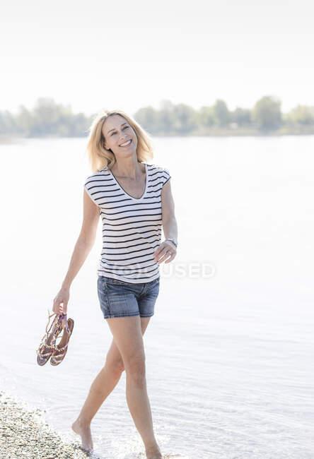 Улыбающаяся взрослая женщина, плывущая по реке — стоковое фото