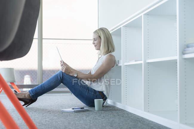 Femme d'affaires occasionnelle assise par terre au bureau à l'aide d'une tablette — Photo de stock