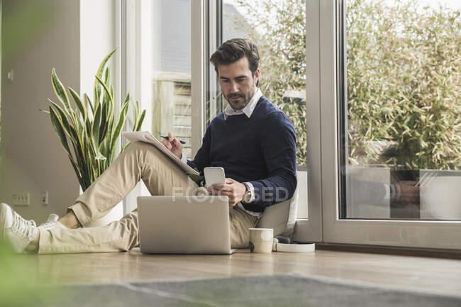 Молодий чоловік сидить у вітальні, спираючись на вікно, працює з ноутбуком, записує нотатки — стокове фото