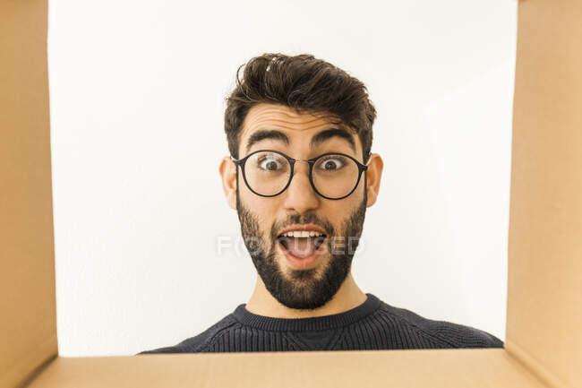 Retrato de un joven sorprendido con barba y gafas mirando a la caja de cartón - foto de stock