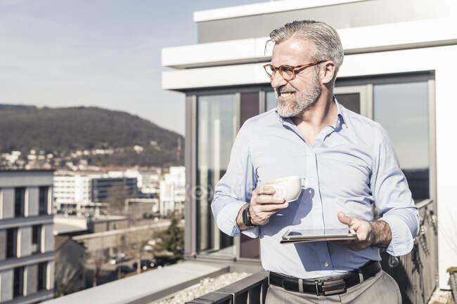 Smiling mature businessman with cup of coffee and tablet on roof terrace — Stock Photo