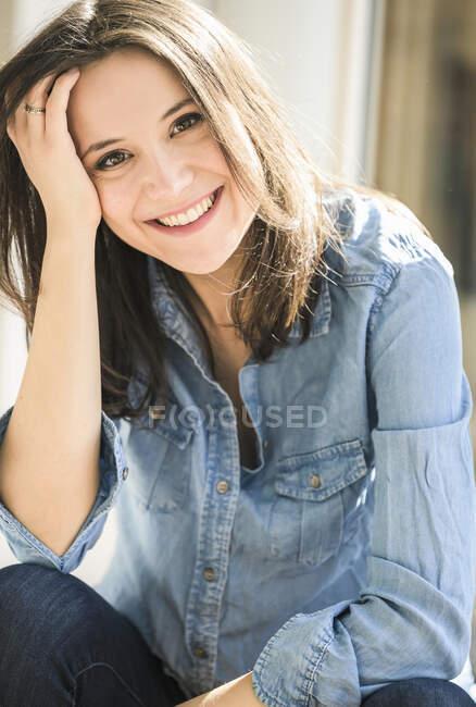 Portrait de femme heureuse portant une chemise en denim à la maison — Photo de stock