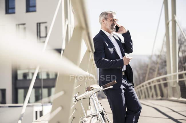 Посмішка дорослого бізнесмена з велосипедом, який розмовляє по мобільному телефону в місті. — стокове фото