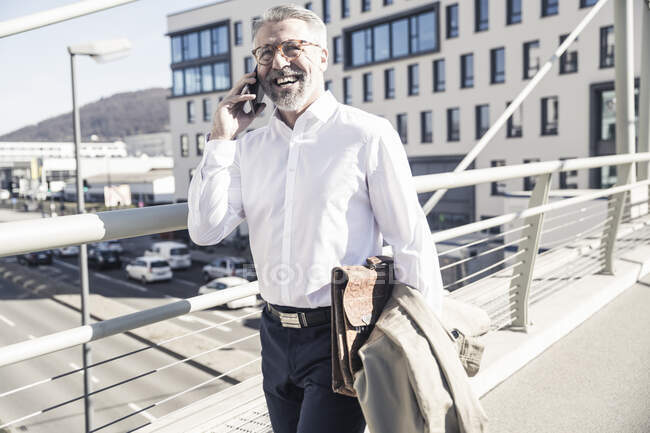 Happy mature businessman talking on cell phone in the city — Stock Photo