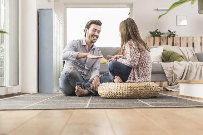 Junger Mann und kleines Mädchen sitzen zu Hause und spielen Papierschere Stein — Stockfoto