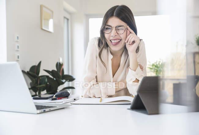Retrato de jovem mulher feliz sentada à mesa em casa cintilando — Fotografia de Stock