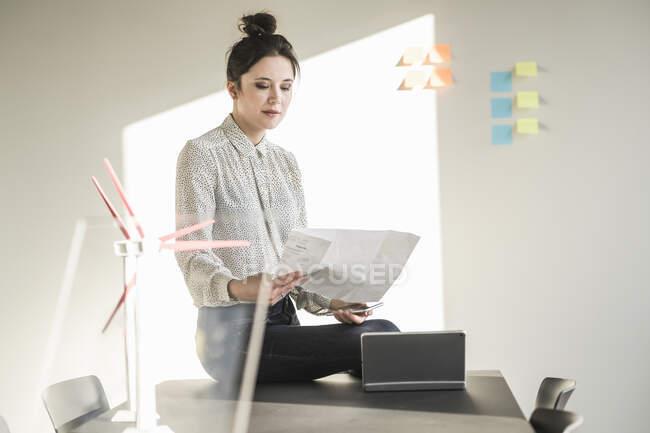 Бизнесмен в офисе план чтения с моделями ветряных турбин на столе — стоковое фото