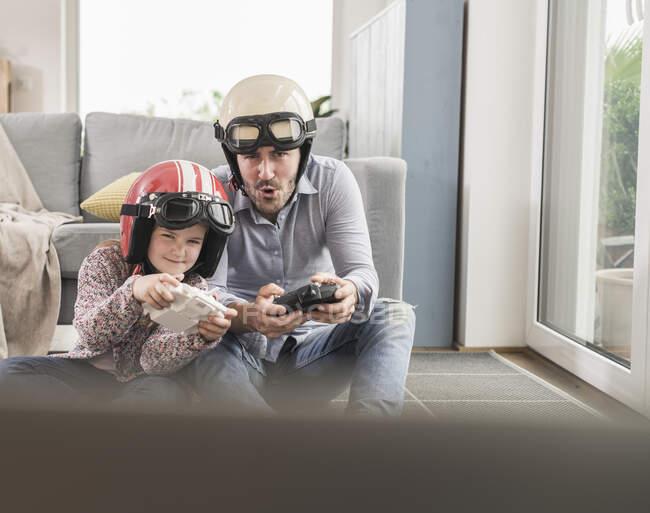 Hombre joven y niña con cascos de ciclista, jugando juego de carreras con consolas de juegos - foto de stock