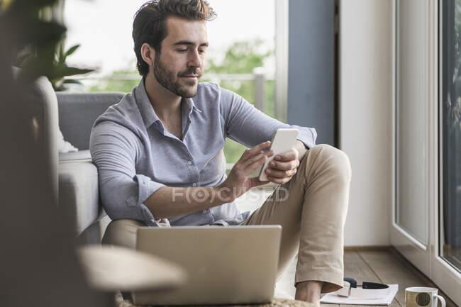 Jeune homme assis à la maison sur le sol, en utilisant un smartphone — Photo de stock
