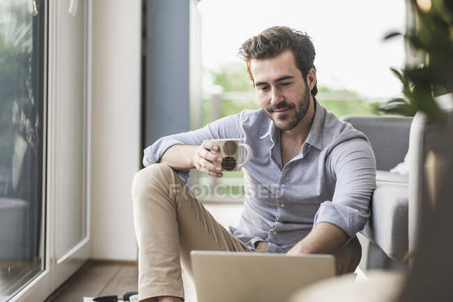 Young man sitting at home on floor, using laptop, drinking coffee — Stock Photo