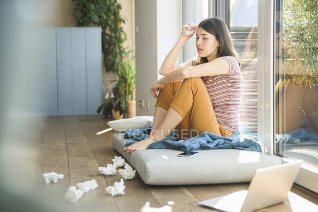 Сумна молода жінка сидить біля вікна з ноутбуком і тканинами. — стокове фото