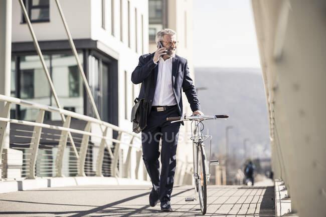 Homme d'affaires mature souriant avec vélo parlant sur un téléphone portable dans la ville — Photo de stock
