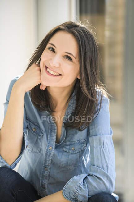 Retrato de mulher feliz vestindo camisa jeans em casa — Fotografia de Stock