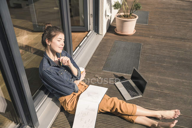 Young woman with closed eyes sitting on terrace at home with laptop and book — Stock Photo