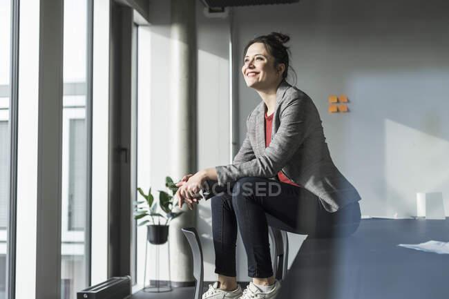 Безробітна жінка сидить за столом у кабінеті і дивиться у вікно. — стокове фото