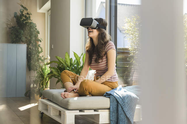 Mujer joven y feliz sentada en la ventana de casa con gafas VR - foto de stock