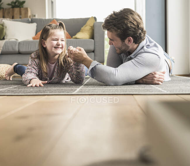 Молодий чоловік і маленька дівчинка лежачі на землі, ручна боротьба. — стокове фото