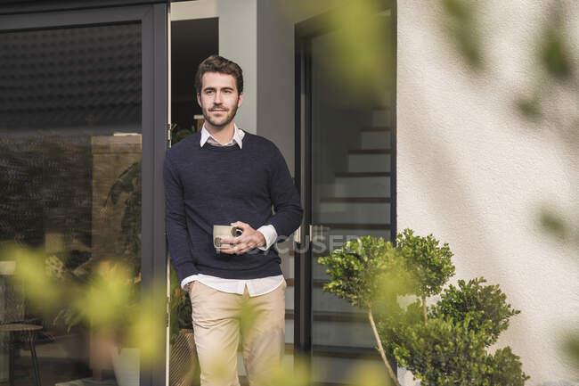 Junger Mann lehnt mit einer Tasse Kaffee in der Tür seines Hauses — Stockfoto