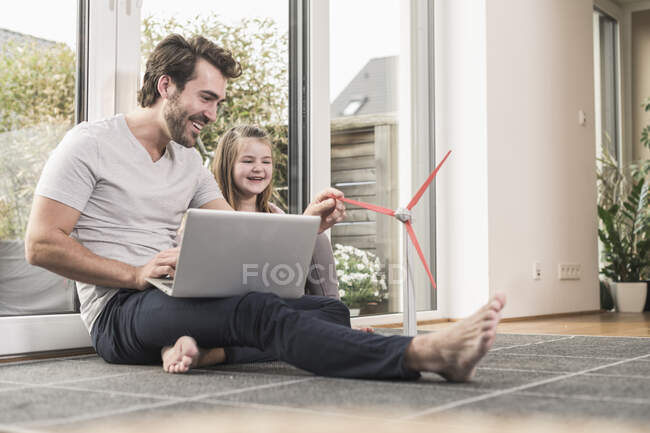 Young man and little girl playing with model of a wind turbine — Stock Photo