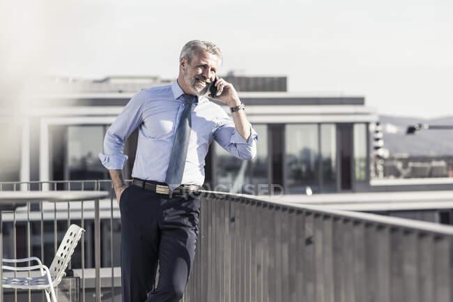 Усміхнений дорослий бізнесмен на терасі даху. — стокове фото