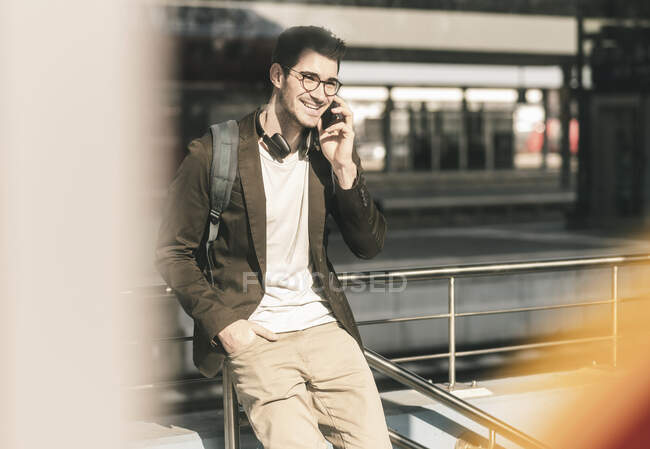Smiling young man talking on cell phone at the station — Stock Photo